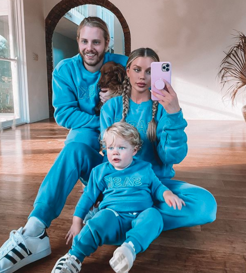Skye Wheatley, partner Lachlan and one-year-old Forest wear blue hue dark Saski Mini and Unisex tracksuit