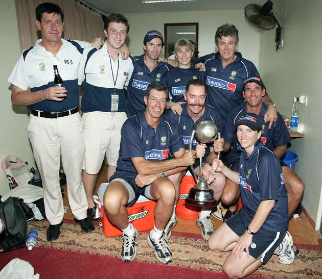 The support team of the Australian cricket team, Team Manager Steve Bernard, Media Manager Jonathan Rose, Fitness Advisor Jock Campbell, Yoga Instructor Kate Turner, Physio Errol Alcott, Coach John Buchanan, Security Manager Reg Dickason, Assistant Coach Tim Nielsen and Masseuse Lucy Frostick with the Border Gavaskar Trophy after day three of the Fourth Test between India and Australia at Wankhede Stadium on November 5, 2004 in Mumbai, India. (Photo by Hamish Blair/Getty Images)