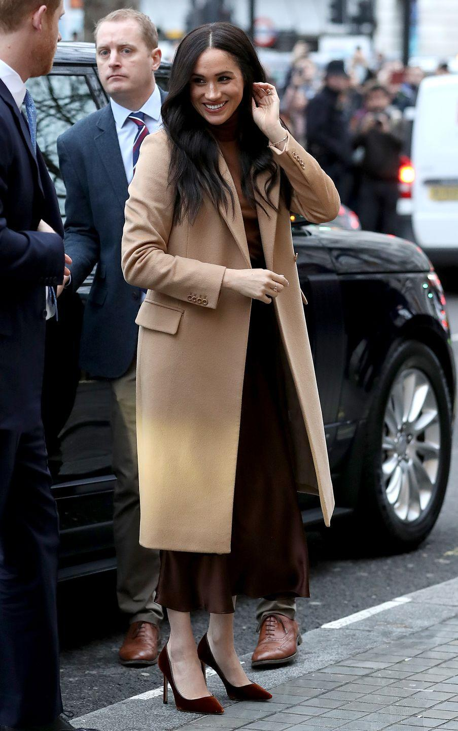 """<p>For the visit, Meghan wrapped up in a Reiss <a href=""""https://www.elle.com/uk/fashion/what-to-wear/articles/g31087/best-camel-coats-to-buy-now-high-street-topshop-mango-warehouse/"""" rel=""""nofollow noopener"""" target=""""_blank"""" data-ylk=""""slk:camel coat"""" class=""""link rapid-noclick-resp"""">camel coat</a>, roll neck tan jumper, a <a href=""""https://www.net-a-porter.com/gb/en/product/1147632?gclsrc=aw.ds&gclsrc=aw.ds&cm_mmc=Google-ProductSearch-UK--c-_-NAP_EN_UK_PLA-_-NAP+-+UK+-+GS+-+Sale+-+1MD+-+Designer+-+FW19+-+CSS--Sale+-+Clothing_INTL&gclid=Cj0KCQiA9dDwBRC9ARIsABbedBN7UEdmY_HPJszYZ8jikEAxzuCUwTaP-8dzO1UcL2QiyUbav1hoGJMaAureEALw_wcB"""" rel=""""nofollow noopener"""" target=""""_blank"""" data-ylk=""""slk:Vince mahogany brown slip midi skirt"""" class=""""link rapid-noclick-resp"""">Vince mahogany brown slip midi skirt</a> and burgundy-coloured suede pumps by Jimmy Choo.</p><p>The visit to Canada House marked the royal's first with Prince Harry since their Christmas holidays spent in Canada in 2019. </p>"""