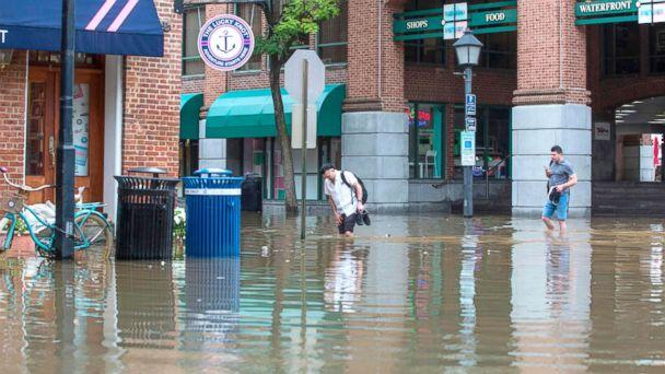 PHOTO: People cross the street as water floods outside buildings in Old Town Alexandria, Va., Sept. 11, 2018. (Zach Gibson/AFP/Getty Images)
