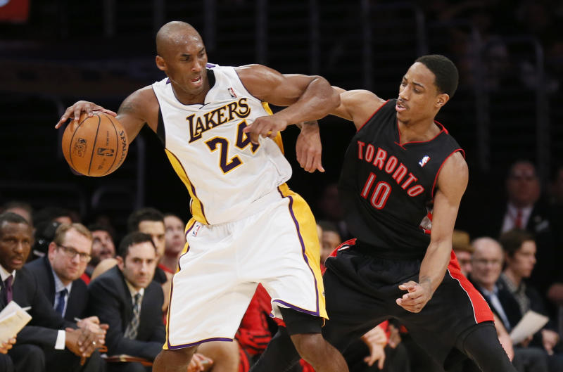 Los Angeles Lakers' Kobe Bryant, left, dribbles the ball as he is defended by Toronto Raptors' DeMar DeRozan, right, during the second half of an NBA basketball game in Los Angeles, Sunday, Dec. 8, 2013. It was Bryant's first game back after a torn left Achilles tendon injury. (AP Photo/Danny Moloshok)