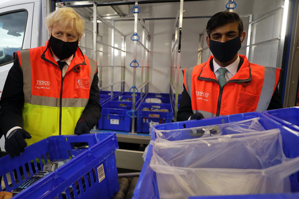 Britain's prime minister Boris Johnson and chancellor Rishi Sunak load a delivery van with baskets of shopping during a visit to a tesco.com distribution centre in London, on 11 November. Photo: Kirsty Wigglesworth/AP