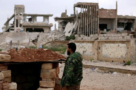 A rebel fighter stands near damaged buildings in rebel-held area of southern city of Deraa