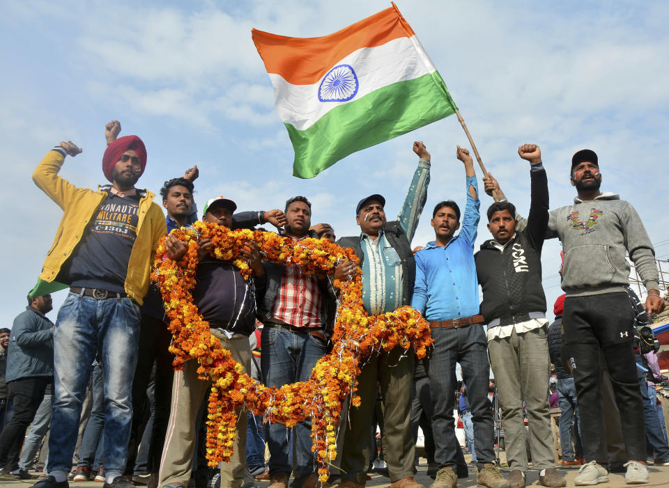 Indians shout slogans carrying a huge garland as they wait to welcome Indian pilot at India Pakistan border at Wagah, 28 kilometers (17.5 miles) from Amritsar, India, Friday, March 1, 2019. Pakistan is preparing to hand over a captured Indian pilot as shelling continued for a third night across the disputed Kashmir border even as the two nuclear-armed neighbors seek to defuse the most serious confrontation in two decades. (AP Photo/Prabhjot Gill)