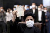 Ebrahim Raisi, head of Iran's judiciary shows his identification document while registering his name as a candidate for the June 18 presidential elections at elections headquarters of the Interior Ministry in Tehran, Iran, Saturday, May 15, 2021. (AP Photo/Ebrahim Noroozi)