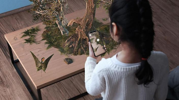 Young girl projecting animal habitat from AR app Museum Alive from her phone