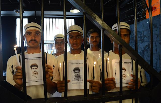 Indian waiters dressed like prison inmates at a jail themed restaurant pose for a picture holding a photo of the late Sarabjit Singh as they pay tribute to him in Ahmedabad on May 2, 2013. An Indian man on death row in Pakistan for spying died nearly a week after he was attacked by fellow prisoners, who were swiftly charged with murder as New Delhi demanded justice. Sarabjit Singh, who was sentenced 16 years ago over deadly bombings, died in the early hours as a result of the savage assault in Lahore's Kot Lakhpat jail, a senior doctor at Jinnah hospital in the eastern city told AFP. AFP PHOTO / Sam PANTHAKY (Photo credit should read SAM PANTHAKY/AFP/Getty Images)
