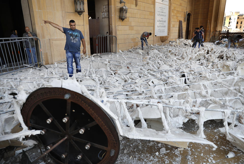 People remove debris from a damaged mosque a day after an explosion hit the seaport of Beirut, Lebanon, Wednesday, Aug. 5, 2020. Residents of Beirut confronted a scene of utter devastation on Wednesday, a day after a massive explosion at the port rippled across the Lebanese capital, killing at least 100 people, wounding thousands and leaving entire city blocks flooded with glass and rubble. (AP Photo/Hussein Malla)