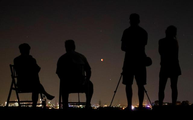 <p>People in a field watch a blood moon in the sky over the skyline of Frankfurt, Germany, July 27, 2018. (Photo: Kai Pfaffenbach/Reuters) </p>