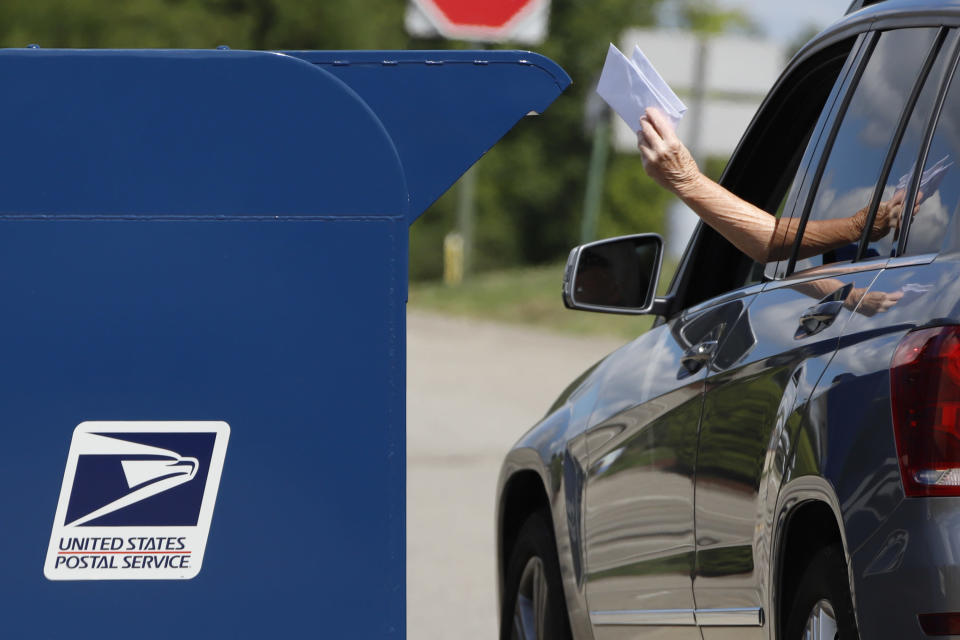 FILE - In this Aug. 19, 2020, file photo, a person deposits mail in a box outside United States Post Office in Cranberry Township, Pa. U.S. Postal Service records show delivery delays have persisted across the country as millions of Americans began voting by mail, raising the possibility of ballots being rejected because they arrive too late. Parts of the politically coveted battleground states of Wisconsin, Michigan, Pennsylvania and Ohio fell short of delivery goals by wide margins as the agency struggles to regain its footing after a tumultuous summer. (AP Photo/Gene J. Puskar, File)