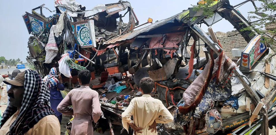 Local residents look at the wreckage of a bus at the site of an accident near Dera Ghazi Khan, Pakistan, Monday, July 19, 2021. A speeding bus carrying mostly laborers traveling home for a major Muslim holiday rammed into a container truck on a busy highway in central Pakistan, killing and injuring dozens, police and rescue officials said. (AP Photo/Saleem Khan)