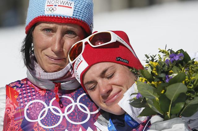 Norway's gold medal winner Marit Bjoergen, left, hugs bronze medal winner Heidi Weng during the flower ceremony of the women's cross-country 15k skiathlon at the 2014 Winter Olympics, Saturday, Feb. 8, 2014, in Krasnaya Polyana, Russia. (AP Photo/Dmitry Lovetsky)