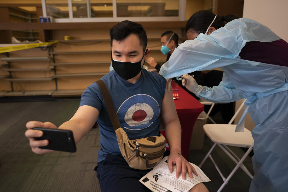 FILE - In this April 12, 2021, file photo, Freeson Wong, 31, takes a selfie as he receives a dose of the Moderna vaccine at a vaccination center in the Chinatown neighborhood of Los Angeles. The United States opened more distance between itself and much of the rest of the world on Thursday, April 15, nearing the 200 millionth vaccine administered in a months-long race to protect the population against COVID-19, even as other countries, rich and poor, struggle with stubbornly high infection rates and deaths. (AP Photo/Jae C. Hong, File)