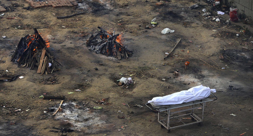 A dead body waits to be cremated as multiple funeral pyres of those who died of COVID-19 burn at a ground that has been converted into a crematorium for mass cremation of coronavirus victims, in New Delhi, India, Wednesday, April 21, 2021. Delhi has been cremating so many bodies of coronavirus victims that authorities are getting requests to start cutting down trees in city parks, as a second record surge has brought India's tattered healthcare system to its knees.(AP Photo)