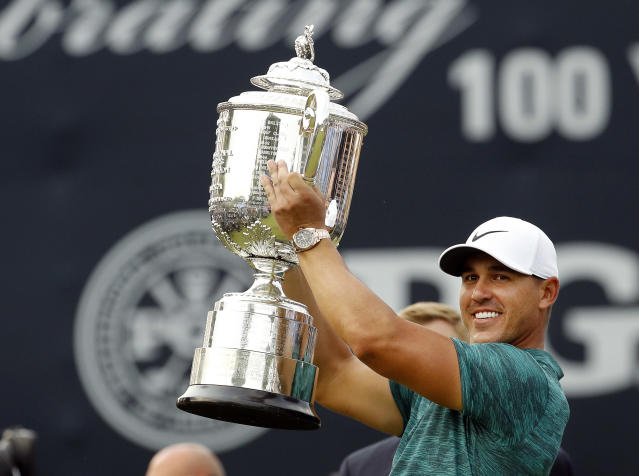 FILE - In this Aug. 12, 2018, file photo, Brooks Koepka lifts the Wanamaker Trophy after winning the PGA Championship golf tournament at Bellerive Country Club, in St. Louis. Koepka has won PGA Tour player of the year on the strength of his two major championships. (AP Photo/Charlie Riedel, File)