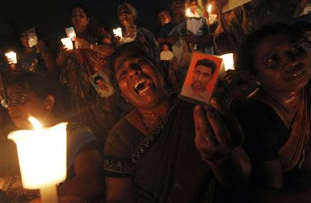 A Tamil woman cries as she holds up an image of her family member who disappeared during the civil war with the Liberation Tigers of Tamil Eelam (LTTE) at a vigil to commemorate the international day of the disappeared in Colombo August 30, 2013. REUTERS/Dinuka Liyanawatte