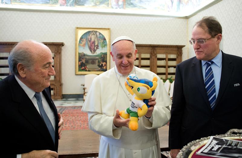 """In this photo provided by the Vatican newspaper L'Osservatore Romano Pope Francis is presented with Fuleco, the Official Mascot of the FIFA 2014 World Cup in Brazil during a meeting with FIFA president Joseph Sepp Blatter, left, at the Vatican Friday, Nov. 22, 2013. Blatter said he responded to the pope's request for FIFA to help the favelas, or slums, of Rio de Janeiro during the 2014 World Cup, with a promise to """"do what we can.""""(AP Photo/L' Osservatore Romano, ho)"""