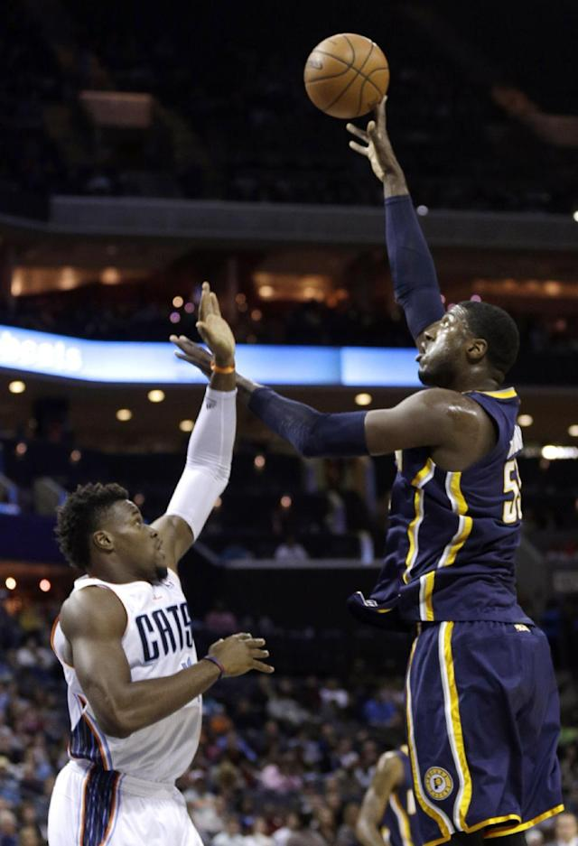 Indiana Pacers' Roy Hibbert, right, shoots over Charlotte Bobcats' Jeff Adrien, left, during the first half of an NBA basketball game in Charlotte, N.C., Wednesday, Nov. 27, 2013. (AP Photo/Chuck Burton)