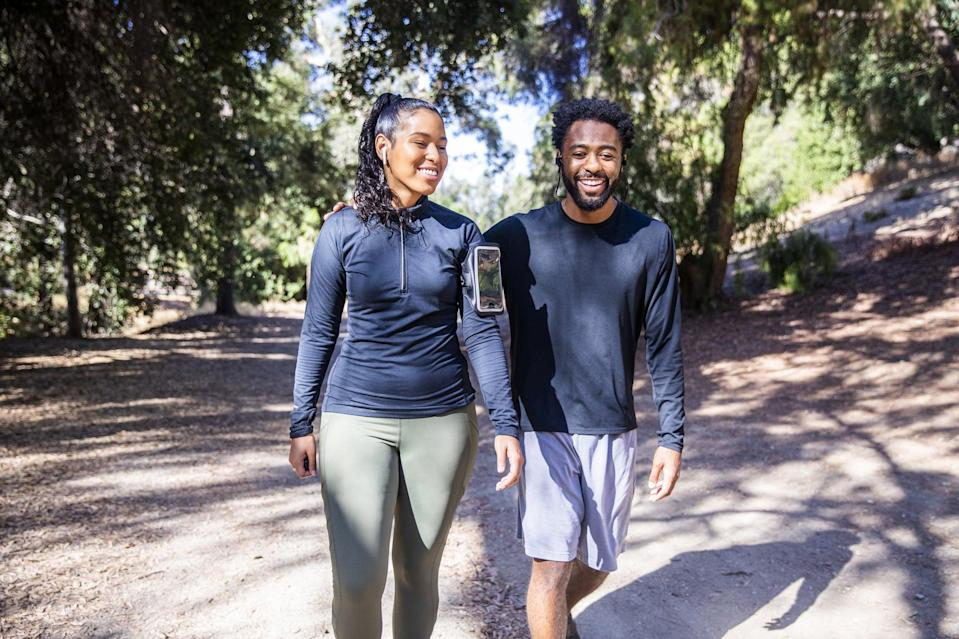 A black man and Latina woman walking on a trail after a workout