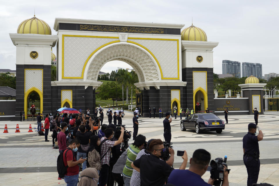 Police salute to Sultan of Perlis, inside a black car, as the convoy arriving National Palace in Kuala Lumpur, Malaysia, Sunday, Oct. 25, 2020. Malay rulers hold a special meeting on Sunday to discuss the government's plan to declare an emergency to tackle the worsening COVID-19 situation. (AP Photo/Vincent Thian)