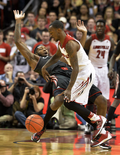 Cincinnati's Titus Rubles, left, is knocked down by Louisville's Russ Smith during the first half of an NCAA college basketball game Thursday, Jan. 30, 2014, in Louisville, Ky. (AP Photo/Timothy D. Easley)