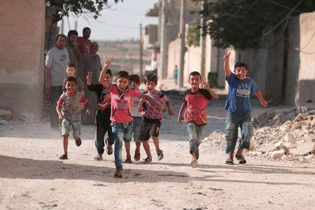 Children flash victory signs as they play in Manbij, in Aleppo Governorate, Syria, August 9, 2016. REUTERS/Rodi Said