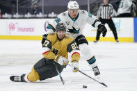 Vegas Golden Knights defenseman Shea Theodore (27) vies for the puck with San Jose Sharks right wing Timo Meier (28) during the third period of an NHL hockey game Wednesday, April 21, 2021, in Las Vegas. (AP Photo/John Locher)