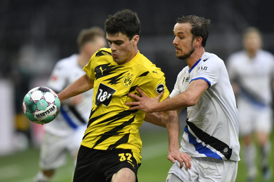 Dortmund's Giovanni Reyna, left, challenges for the ball with Arminia's Manuel Prietl during the German Bundesliga soccer match between Borussia Dortmund and Arminia Bielefeld in Dortmund, Germany, Saturday, Feb. 27, 2021. (AP Photo/Martin Meissner, Pool)