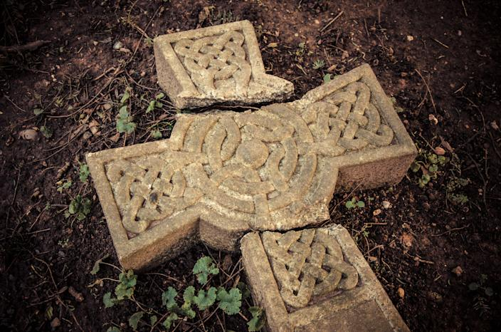 Ancient broken Celtic cross laying on the ground at an English graveyard.