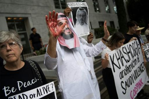 A demonstrator dressed as Saudi Crown Prince Mohammed bin Salman (C) with blood on his hands protests outside the Saudi Embassy in Washington, DC, on October 8, 2018