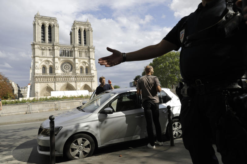Police officers clear the area around Notre Dame cathedral in Paris, Monday, Aug. 12, 2019. Authorities started clearing the area around Notre Dame ahead of decontamination and cleanup work which will resume on Aug. 19 after new equipment and stricter safety procedures ensure workers are not exposed to unsafe levels of lead following the fire earlier this year. (AP Photo/Lewis Joly)