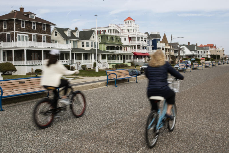 Cyclists ride their bicycles in Cape May, N.J., where some locals, fearing infection and an overwhelming of already-stretched resources, are yanking the welcome mat from city dwellers with beach houses. (AP Photo/Matt Rourke)