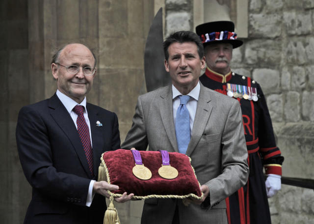 Sebastian Coe, right, chairman of the London 2012 Organizing Committee, and Jan du Plessis, left, Rio Tinto mining company chairman, pose for the photographers holding a gold medal of the Games, during a photo op at the Tower of London, in London, Monday, July 2, 2012. The company is responsible for the production of the precious metals for the London 2012 Games, and has handed over the final Olympic and Paralympic medals to LOCOG for secure storage in the vaults at the Tower of London during the Games. The gold, silver and bronze medals which will be awarded to the athletes at Games-times, will remain there until they are needed for the Victory Ceremonies. In total, 4,700 medals have been produced and will be awarded in 805 Victory Ceremonies that will take place in over 30 London 2012 venues across the UK. (AP Photo/Lefteris Pitarakis)