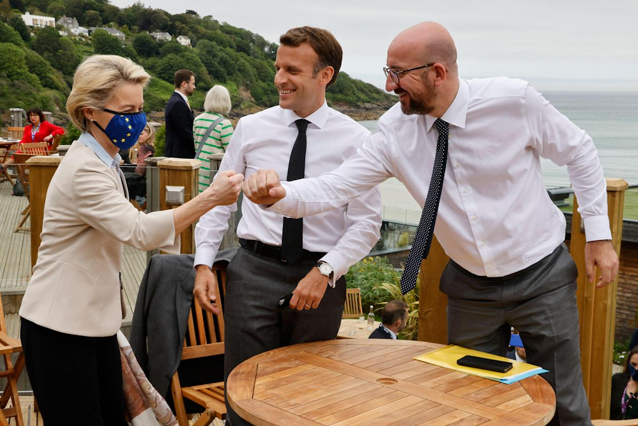 TOPSHOT - (L-R) President of the European Commission Ursula von der Leyen, France's President Emmanuel Macron, and President of the European Council Charles Michel bump fists during an EU coordination meeting in advance of the start of the G7 summit in Carbis bay, Cornwall on June 11, 2021. (Photo by Ludovic MARIN / AFP) (Photo by LUDOVIC MARIN/AFP via Getty Images)