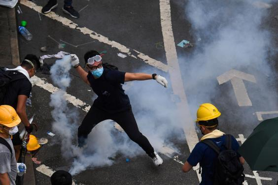 A protester throws back a tear gas during clashes with police outside the government headquarters in Hong Kong on June 12, 2019 (AFP/Getty Images)