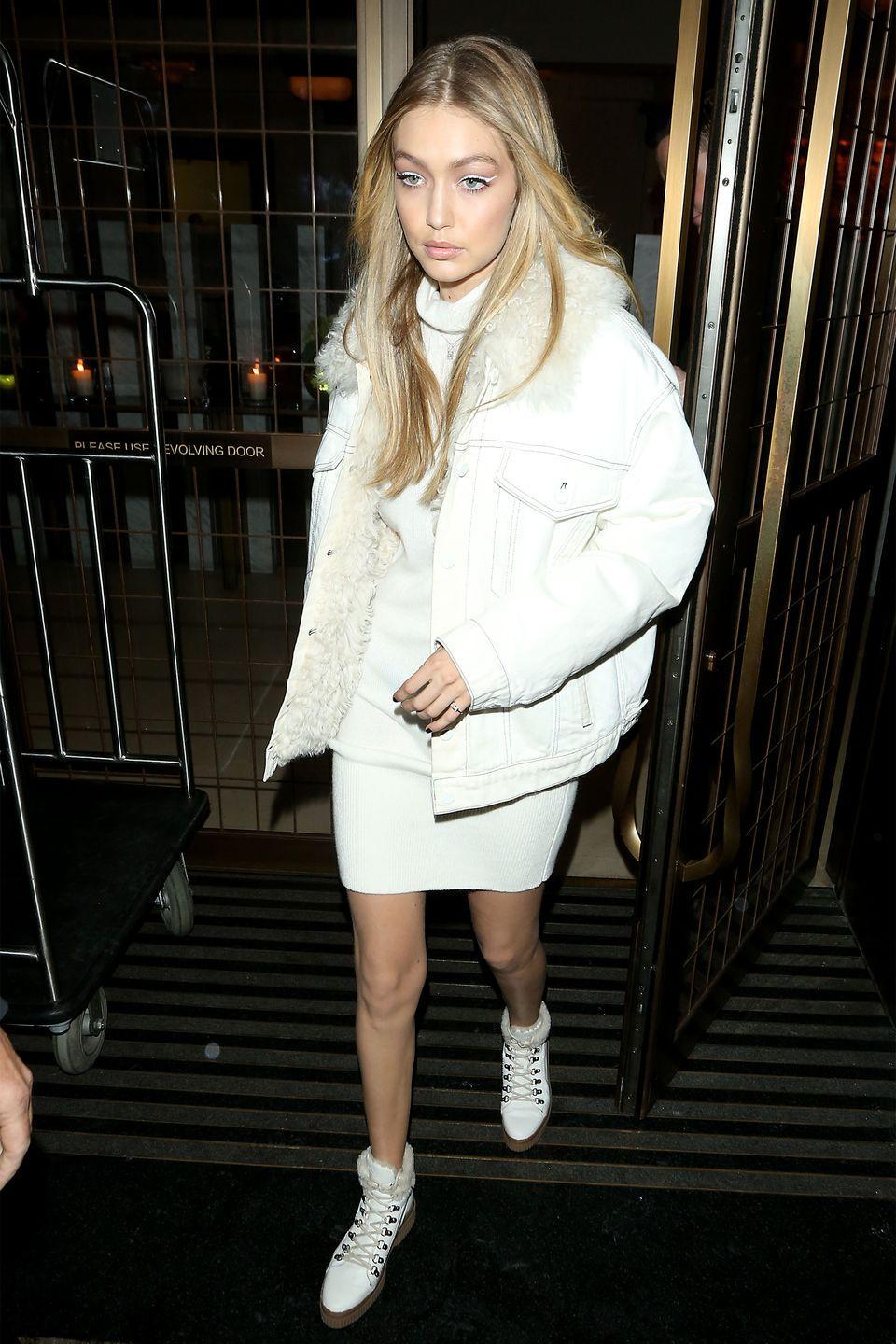<p>In a shearling-lined denim jacket with a sweater dress, Tod's leather combat boots and Messika Jewelry rings while out in London.</p>