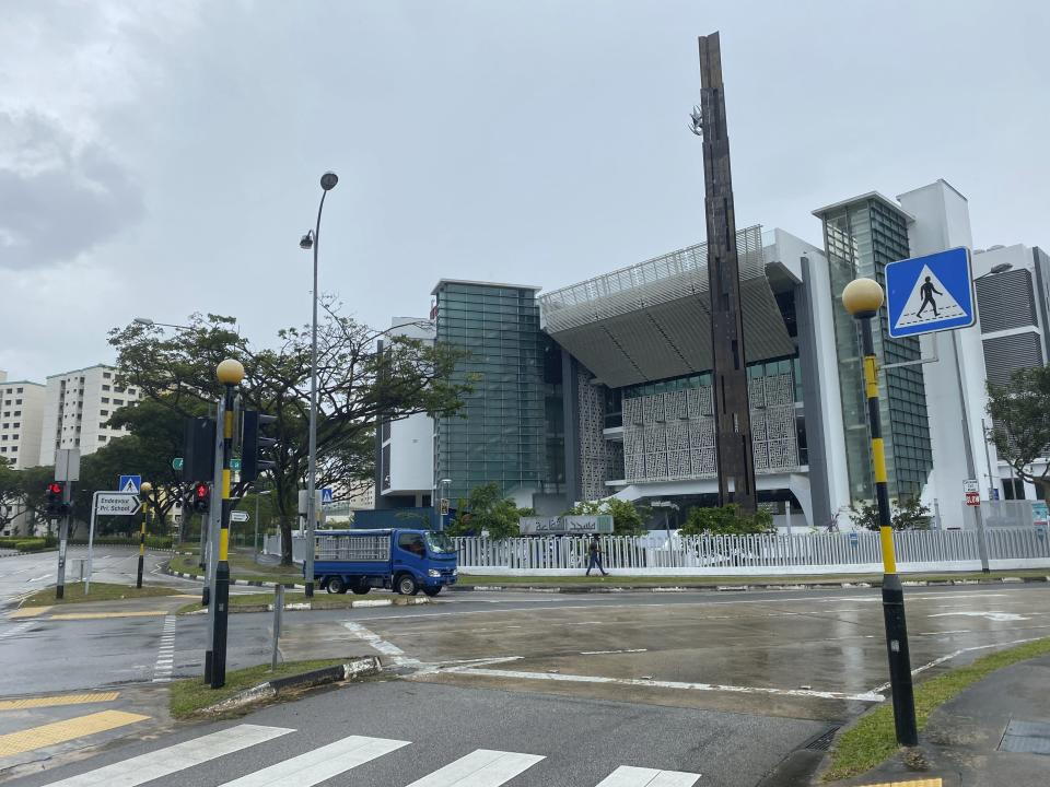 A van passes in front of the Assyafaah Mosque in Singapore, Thursday, Jan. 28, 2021. Two Singapore mosques at the center of a foiled terrorist attack by a 16-year-old student stayed open Thursday as police stepped up patrols around the district. (AP Photo/Annabelle Liang)