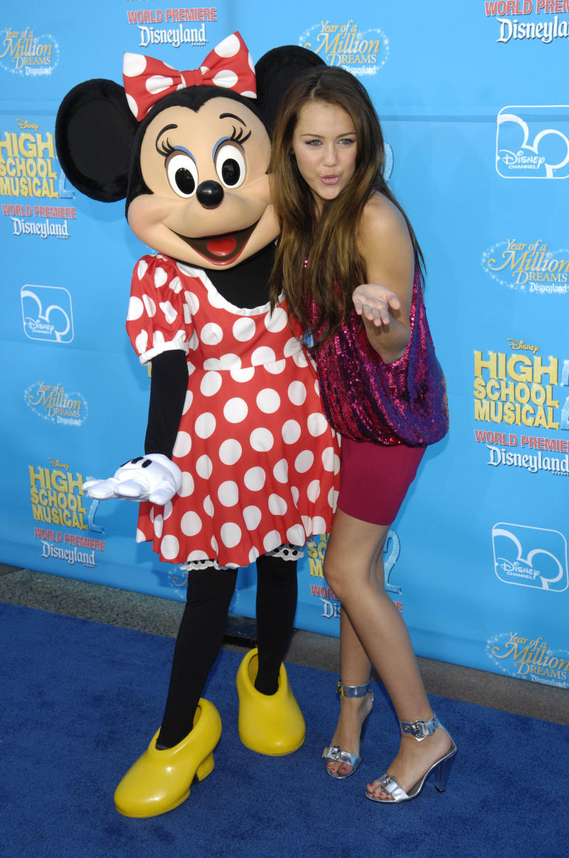 "Actress Miley Cyrus, right, is seen with character Minnie Mouse during arrivals to the premiere of ""High School Musical 2"" at Disneyland in Anaheim, Calif., Tuesday, Aug. 14, 2007. (AP Photo/Chris Pizzello)"