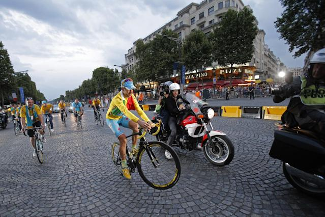 2014 Tour de France cycling race winner Italy's Vincenzo Nibali pulls a wheelie during the team parade of the Tour de France cycling race in Paris, France, Sunday, July 27, 2014. (AP Photo/Christophe Ena)