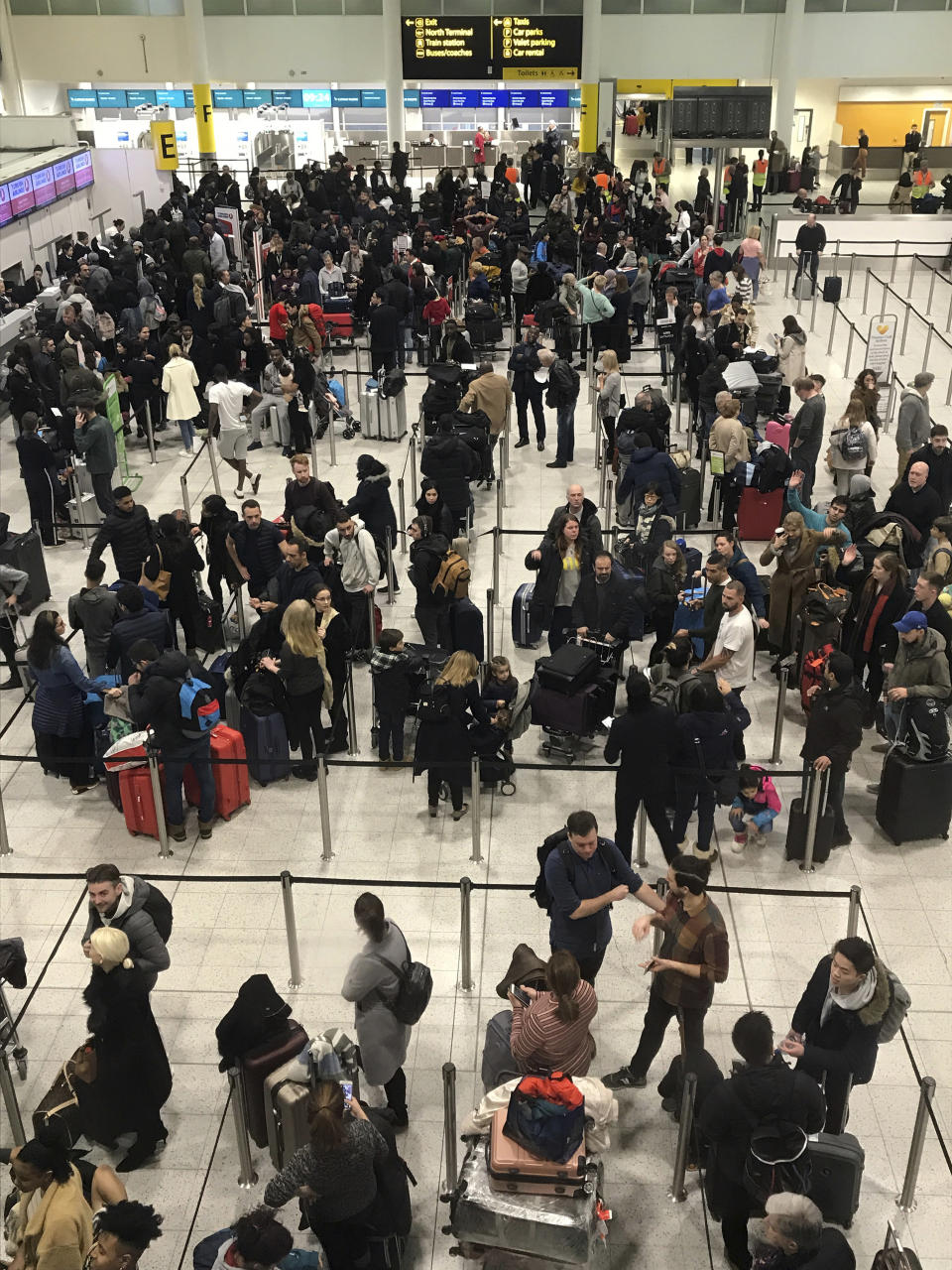 Passengers wait to check in at Gatwick Airport in England, Friday, Dec. 21, 2018. Flights resumed at London's Gatwick Airport on Friday morning after drones sparked the shutdown of the airfield for more than 24 hours, leaving tens of thousands of passengers stranded or delayed during the busy holiday season.(AP Photo/Kirsty Wigglesworth)