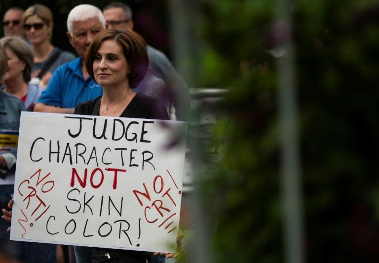"""A woman holds up a sign at a rally against teaching """"critical race theory"""" in schools, in Leesburg, Virginia on June 12, 2021"""