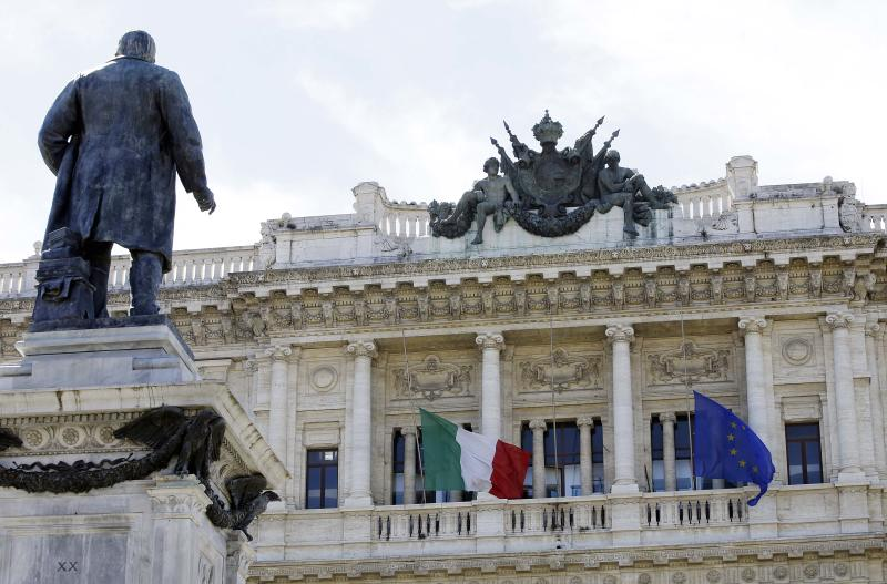 The Italian flag, left, and the EU flag, are at half-mast in memory of Sunday's bus crash victims, on the Court of Cassation building where former Italian Premier Silvio Berlusconi's case on tax fraud will be decided, in Rome, Tuesday, July 30, 2013. Berlusconi's political fate is in the hands of Italy's highest court, which is preparing to hear arguments in the former premier's fraud conviction. Berlusconi has been convicted of tax fraud in a complex TV rights transaction for his Mediaset network, and sentenced to four-years in prison with a five-year ban on public office. This is his final appeal. (AP Photo/Gregorio Borgia)