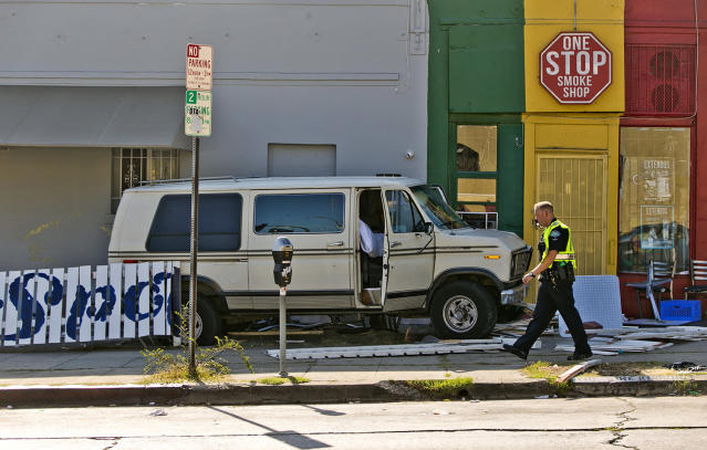 <p>An official walks by a van that plowed into a group of people injuring several on a Los Angeles sidewalk on Sunday, July 30, 2017. A witness to the crash told The Associated Press the van jumped a curb and careened into a group of people eating outside The Fish Spot restaurant in the city's Mid-Wilshire neighborhood. (AP Photo/Damian Dovarganes) </p>