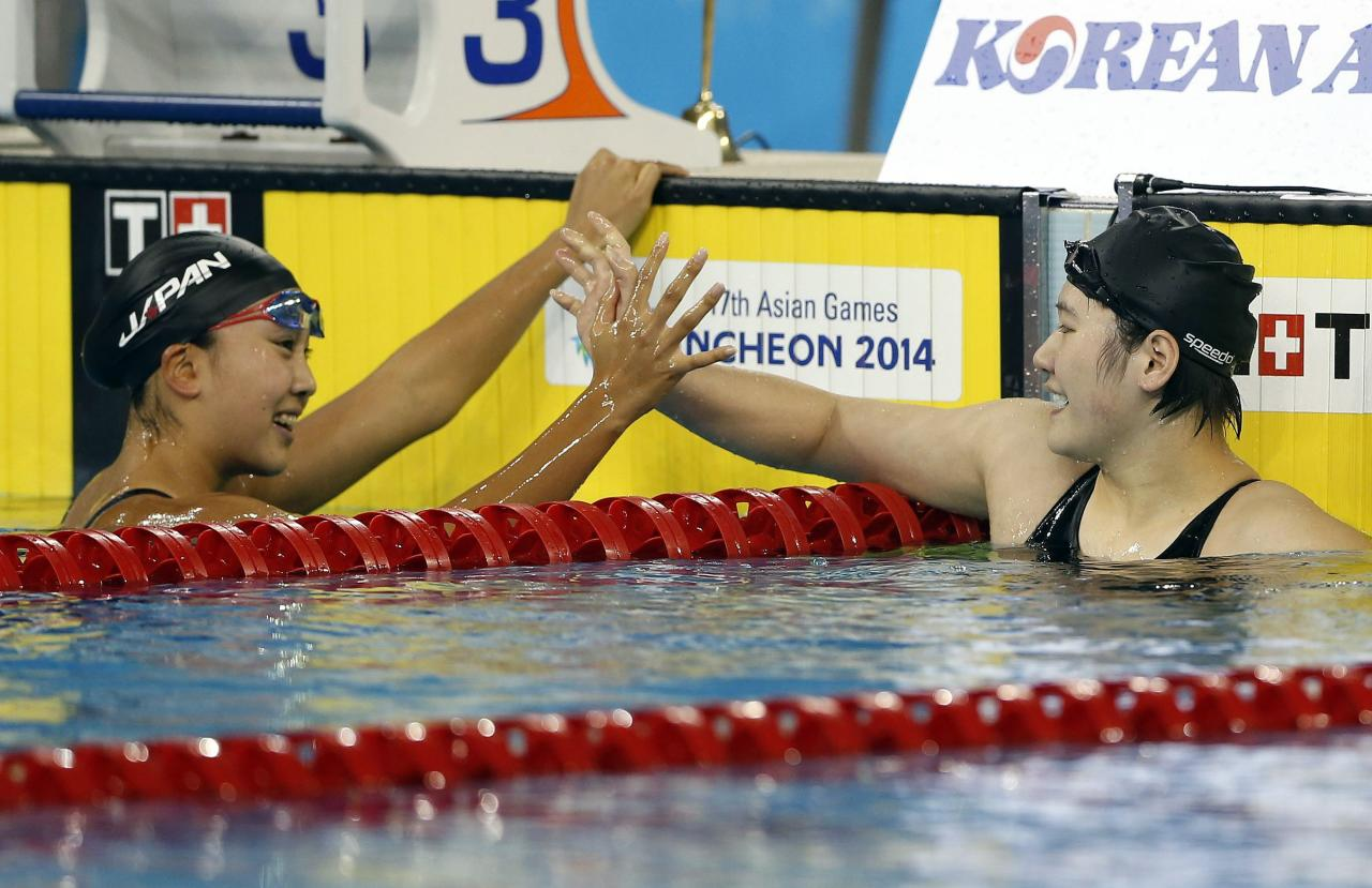 Japan's Kanako Watanabe (L) congratulates China's Ye Shiwen on winning the women's 200m individual medley final swimming competition at the Munhak Park Tae-hwan Aquatics Center during the 17th Asian Games in Incheon September 26, 2014. REUTERS/Tim Wimborne (SOUTH KOREA - Tags: SPORT SWIMMING)