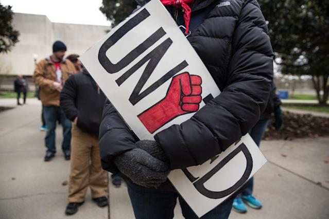 "<p>A striking teacher hold a ""United"" signs= during a rally outside the West Virginia Capitol in Charleston, W.Va., on Friday, March 2, 2018. (Photo: Scott Heins/Bloomberg via Getty Images) </p>"