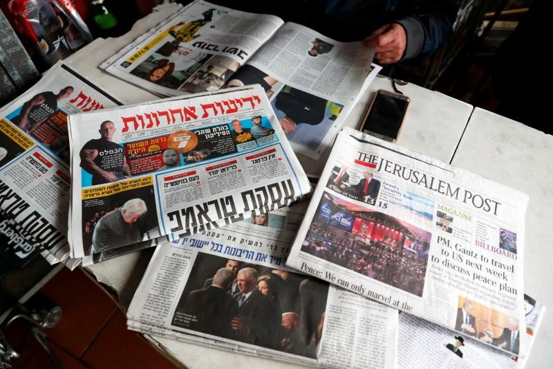 A man sits in a coffee shop next to the main Israeli Newspapers in Jerusalem