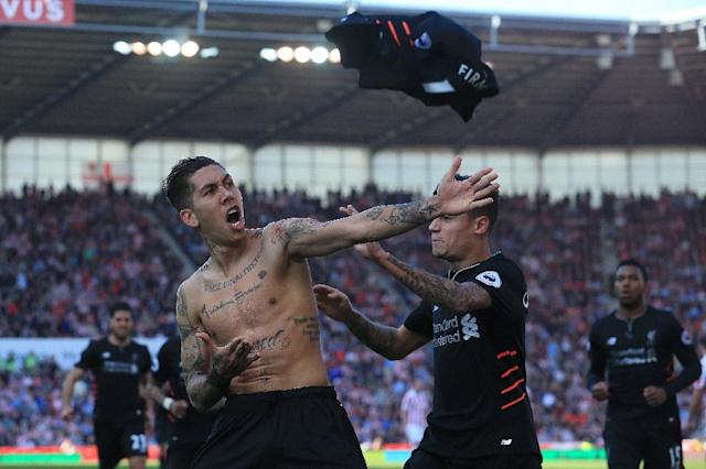 Liverpool's Brazilian midfielder Roberto Firmino (L) celebrates scoring his team's second goal against Stoke City in Stoke-on-Trent, central England on April 8, 2017 (AFP Photo/Lindsey PARNABY)