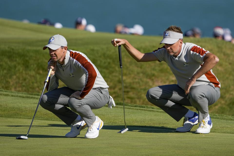 Team Europe's Ian Poulter and Team Europe's Rory McIlroy line up a putt on the sixth hole during a four-ball match the Ryder Cup at the Whistling Straits Golf Course Saturday, Sept. 25, 2021, in Sheboygan, Wis. (AP Photo/Jeff Roberson)