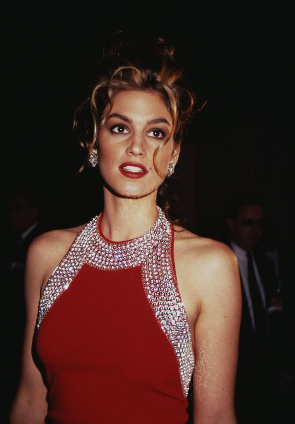 <p>The supermodel donned a scarlet halter neck gown embellished with crystals, in 1993.</p>