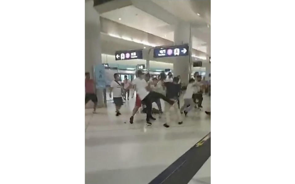 This Sunday, July 21, 2019, image taken from a video, shows confrontation between masked assailants and protesters at Yuen Long MTR train station in Hong Kong. Protesters trying to return home were attacked inside a train station by assailants who appeared to target the pro-democracy demonstrators. (Lam Cheuk-ting via AP)